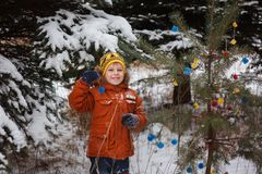 Cute little boy playing with snow in winter forest. Stock Photo
