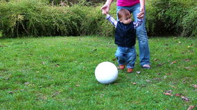 Cute little boy playing with soccer ball supported by his mother stock video footage