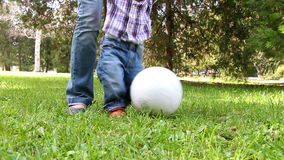 Cute little boy playing with soccer ball supported by his mother stock footage