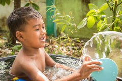 Cute little boy playing splash water while bathing royalty free stock photography