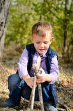 Cute Little Boy Playing with Sticks at the Woods Stock Images