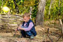 Cute Little Boy Playing with Sticks at the Woods Stock Image