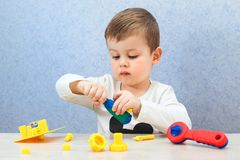 Cute little boy is playing with tools. A toddler working with toy tools. royalty free stock image
