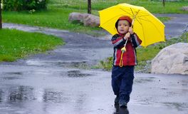 Playing in the rain. Cute little boy playing under the rain with a yellow umbrella Stock Image