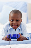 Cute little boy playing video game Stock Photos