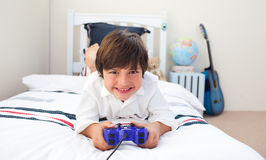 Cute little boy playing video games. In his bedroom Royalty Free Stock Photography