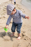Cute little boy playing with watering can on the beach Royalty Free Stock Photography