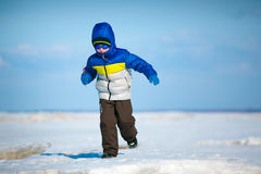 Cute little boy playing on winter beach Stock Photo