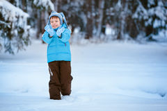 Cute little boy playing on winter forest. Cute little boy playing outdoors on winter forest Stock Photo