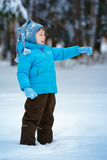 Cute little boy playing on winter forest. Cute little boy playing outdoors on winter forest Stock Image