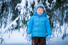 Cute little boy playing on winter forest. Cute little boy playing outdoors on winter forest Royalty Free Stock Photography