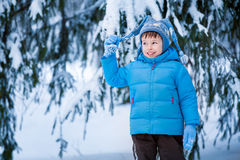 Cute little boy playing on winter forest. Cute little boy playing outdoors on winter forest Royalty Free Stock Images