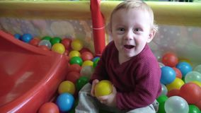 Cute little boy plays ball and smiles in the playing room stock footage
