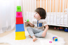 Cute little boy plays educational toy. Little boy playing with educational toy stock photography