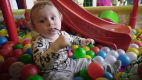 Cute little boy plays the glasses in the playing room stock video footage