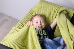 Cute little boy plays in green plaid on couch. In room, top view Royalty Free Stock Image
