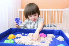 Cute little boy plays kinetic sand at home Stock Photography