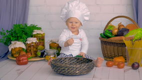 A cute little boy plays in the kitchen with fresh vegetables. stock video