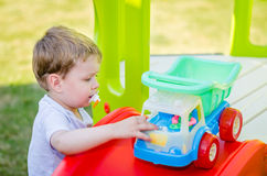 Cute little boy plays with toy car at park Stock Photos