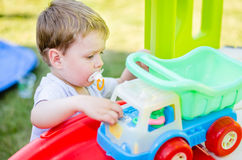 Cute little boy plays with toy car at park Stock Photography