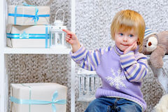 Cute little boy pointing at gift boxes Stock Photo