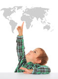 Cute little boy points at world map Royalty Free Stock Image