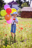 Cute little boy with poppy flower on poppy field with balloons Royalty Free Stock Photos
