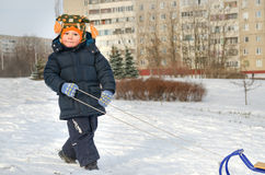 Cute little boy pulling his sled Stock Images