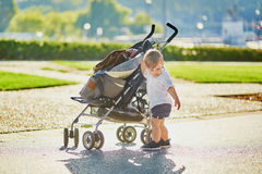 Cute little boy pushing his stroller Royalty Free Stock Photos