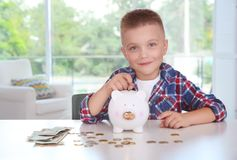 Cute little boy putting coin into piggy bank. Indoors Royalty Free Stock Images