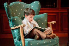 Cute little boy reading book on armchair Stock Image