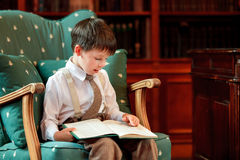 Cute little boy reading book on armchair Stock Photography