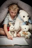 Cute little boy reading book with his favorite toys. Under the blanket Royalty Free Stock Images