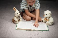 Cute little boy reading book with his favorite toys. On a soft plush blanket Royalty Free Stock Images