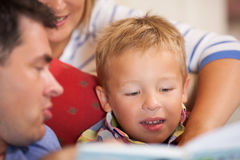 Cute little boy reading a book with his parents Royalty Free Stock Photos