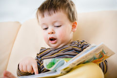 Cute little boy reading book on sofa Stock Images