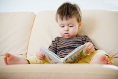 Cute little boy reading book on sofa Stock Photo
