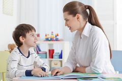 Cute little boy reading book at speech therapist. Office Royalty Free Stock Photo