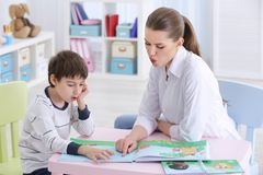 Cute little boy reading book at speech therapist. Office Royalty Free Stock Photos