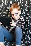 Boy with  tablet. Cute little boy with  reading glasses for a correction of the vision playing on tablet Stock Photography