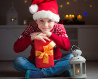 Cute little boy in red hat with gift and  latern waiting Santa C Royalty Free Stock Photo