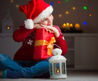 Cute little boy in red hat with gift and  latern waiting Santa C Stock Photos