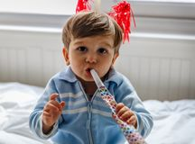A cute little boy with red horns blows a whistle stock photo