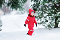 Cute little boy in red winter clothes having fun with snow Royalty Free Stock Image