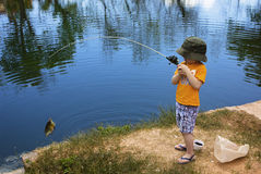 Little Boy Catching a Fish. A cute little boy reeling in a big fish Stock Photo