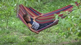 Cute little boy relaxing on colored hammock in green nature stock video