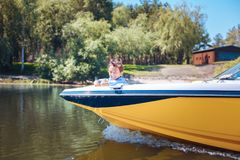 Cute little boy relaxing on motorboat bow. Childlike curiosity. Upbeat little boy relaxing on a motorboat bow and enjoying the view while smiling at the camera stock images