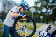 Cute little boy repairing bicycle outdoors Stock Images