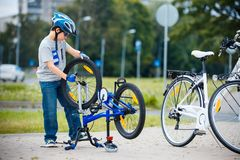 Cute little boy repairing his bicycle outdoors stock photography