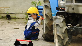 Cute little boy repairing a tractor wheel Stock Photos
